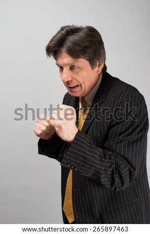 Business man in suit and tie with his fists raised ready for a fight. - stock photo