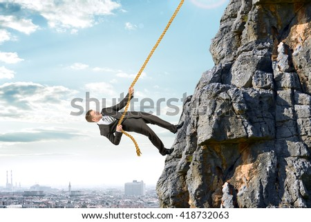 Business man in suit climbs mountain with rope - stock photo