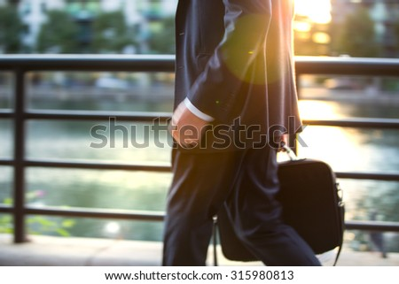 Business man in suit walking against of sunset light, London - stock photo