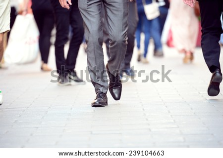 Business man in suit walking on sidewalk - stock photo