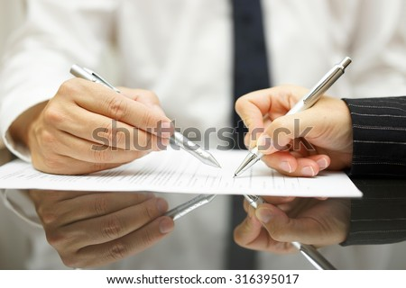Business man is pointing woman where to sign document - stock photo