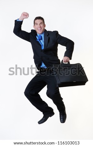 business man jumping in the air with a large smile on his face holding a briefcase - stock photo