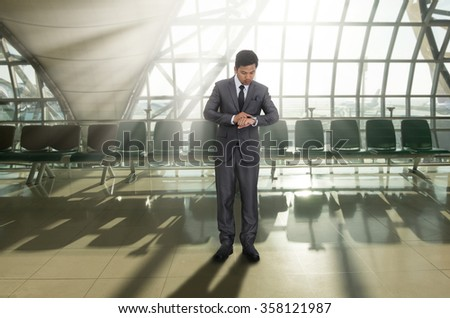 Business man looking at watch on his arm in the airport - stock photo