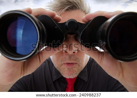 business man looking through binoculars shot close up - stock photo