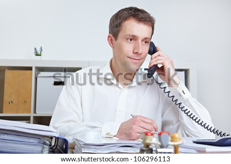 Business man making a call at his desk in the office - stock photo