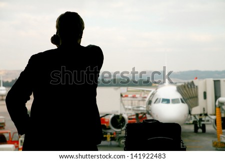 Business man making a last important call before his flight is leaving... - stock photo