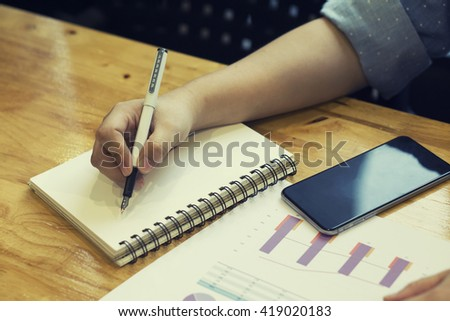 Business man Making some urgent notes.Close-up of man writing something in his note pad while sitting at his working place with document and mobile phone,Signing Contract,vintage tone,selective focus - stock photo