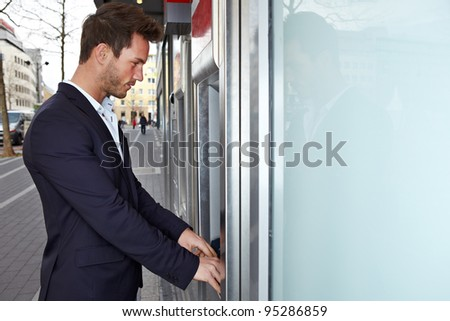 Business man on ATM getting cash payout outdoors in city - stock photo