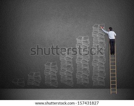 Business man on ladder drawing idea is money concept on wall - stock photo
