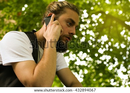 Business man on smart phone in the park. View from below.  - stock photo