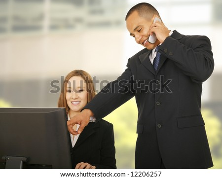 business man on the phone while his coworker looking at computer screen. focus on the man. concept for business deal, communication, mentoring, or team work - stock photo