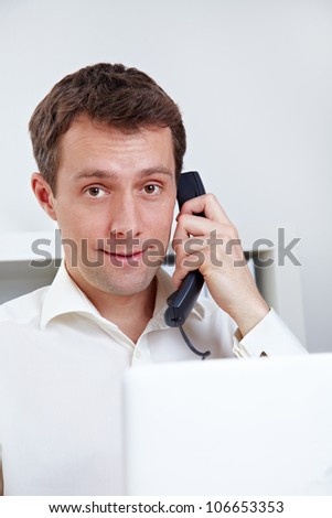 Business man on the phone with laptop at desktop - stock photo