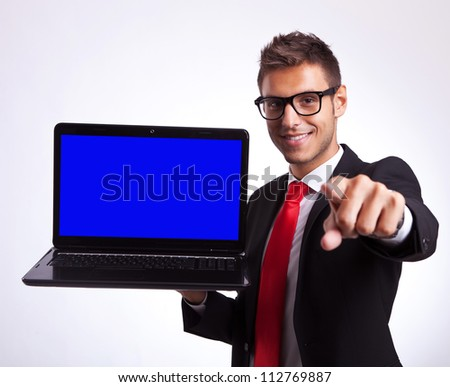 business man or student pointing at you to win a new laptop computer - stock photo
