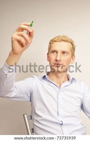 business man painting on a transparent touchscreen with his marker - stock photo