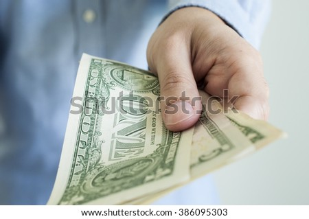Business man paying us dollar bank note - stock photo