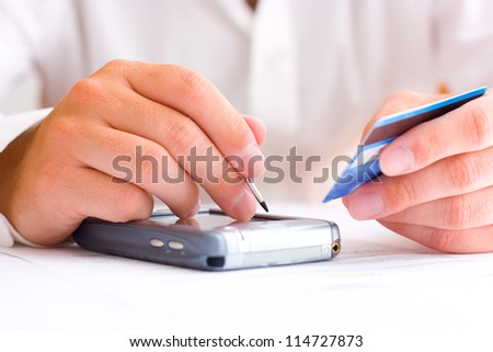 Business man paying with a credit card using a PDA - stock photo