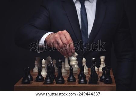 business man playing chess on dark studio background - stock photo