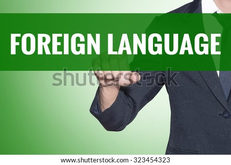 Business man point to Foreign Language word on green tab virtual screen - stock photo