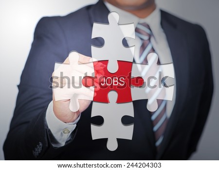 Business Man pointing on jigsaw written word jobs - stock photo