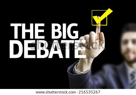 Business man pointing to black board with text: The Big Debate - stock photo