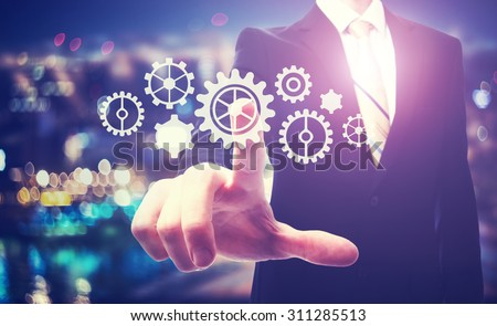 Business man pointing to gears on a blurred city lights background - stock photo