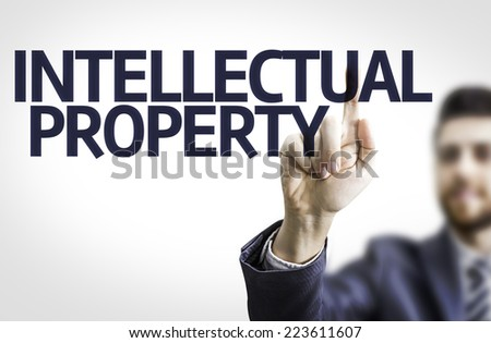 Business man pointing to transparent board with text: Intellectual Property - stock photo