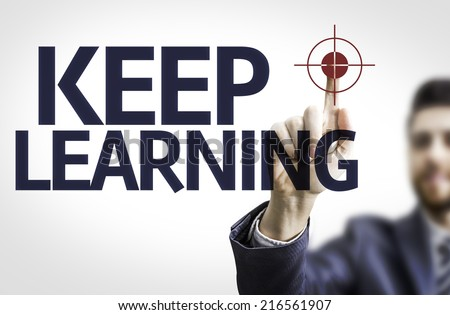 Business man pointing to transparent board with text: Keep Learning - stock photo