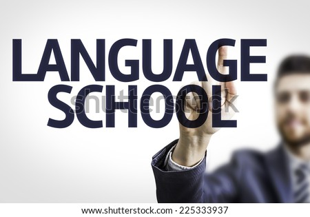 Business man pointing to transparent board with text: Language School - stock photo