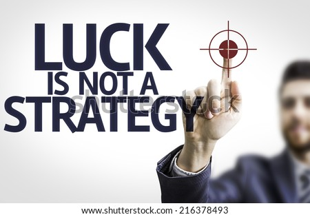 Business man pointing to transparent board with text: Luck is Not a Strategy - stock photo