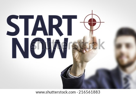 Business man pointing to transparent board with text: Start Now - stock photo