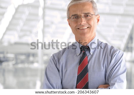 Business man portrait in modern office building. Middle aged man is smiling at the camera and has his arms folded. Closeup head and shoulders only. - stock photo