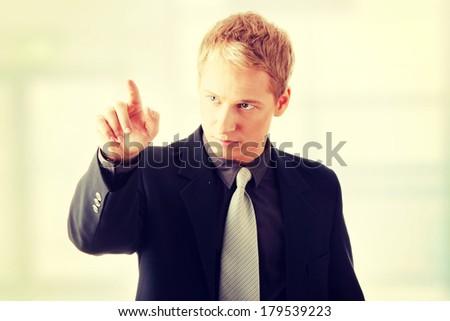 Business man pressing an abstract touchscreen button  - stock photo