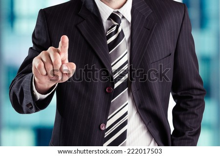 Business man pressing an imaginary button at his office. - stock photo