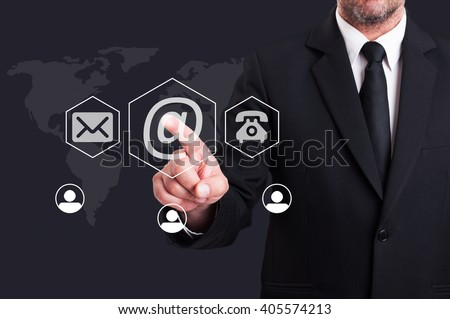 Business man pressing contact us using email digital button on futuristic transparent screen - stock photo
