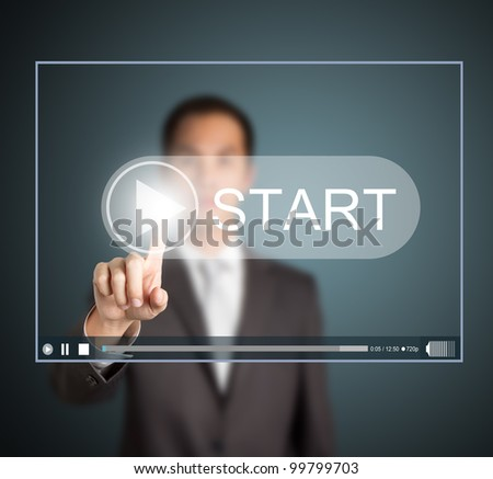 business man pressing start button to play video clip - stock photo