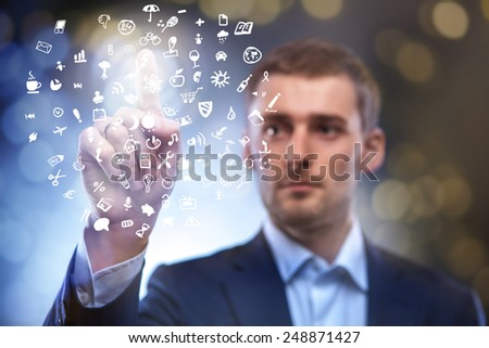 business man pressing touchscreen button with set of icons in air - stock photo