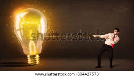 Business man pulling a big bright glowing light bulb concept on background - stock photo