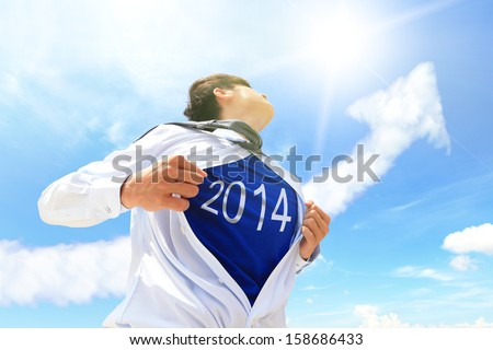Business man pulling his t-shirt open, showing 2014 text with a superhero suit underneath his suit - stock photo