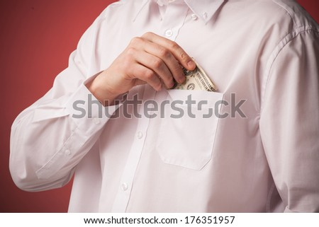 Business man putting dollar banknotes into his pocket on red back - stock photo