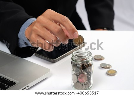 Business man putting golden coins in bottle. Concept of investments. - stock photo