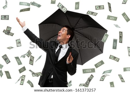 Business man reaching out for raining money - stock photo