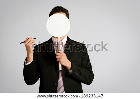 Business: Man Ready To Draw Face On Mask - stock photo