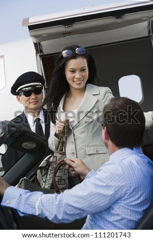 Business man receiving Korean businesswoman with airplane captain in the background at airfield - stock photo