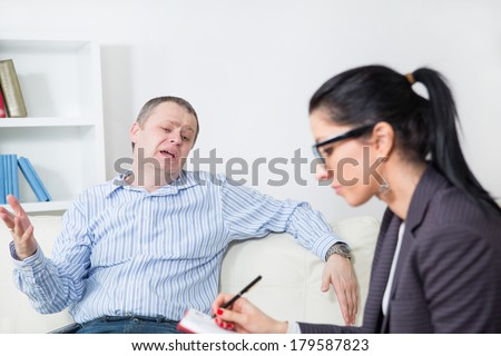 Business man reclining comfortably on a couch talking to his psychiatrist - stock photo