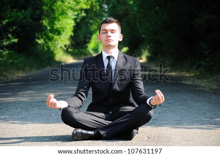 Business man relaxing on road - stock photo