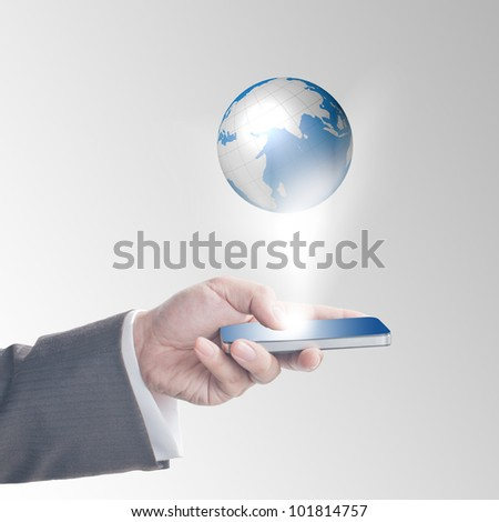 Business man's hand touching on smart phone with glowing digital wire globe - stock photo