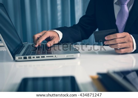 Business man searching and booking hotel for vacation in the next holiday with family or loved one at his office workplace during a break. - stock photo