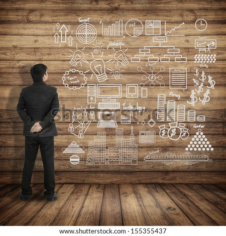 Business man see at Business Concept Chart on Wood wall  - stock photo