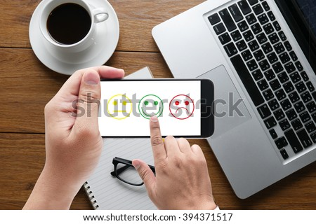 business man select happy on satisfaction evaluation? on hand holding a phone, top view, table computer coffee and book - stock photo