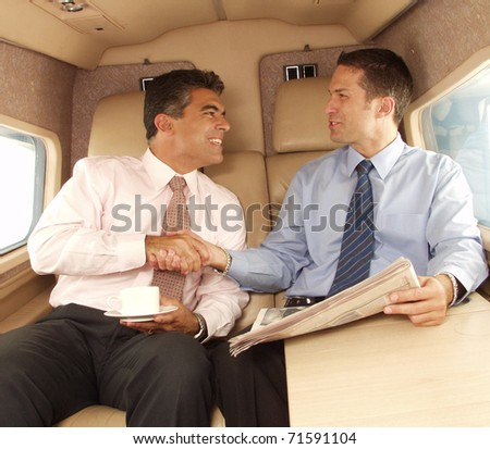 Business man shaking hands and working at private jet. - stock photo